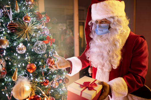 Man in red and white Santa suit and face mask putting square presents wrapped in colorful paper under a holiday decorated evergreen tree